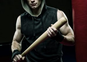 man in black and gray hoodie holding brown wooden stick
